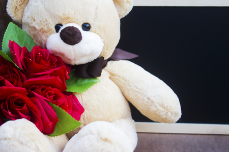Cute teddy Bear toy clutching a red rose in its arms on blackboard background for an anniversary or valentine's celebration with copy space,valentine's day concept.