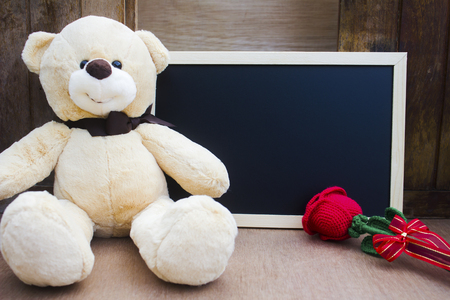Cute teddy Bear with red rose and blackboard on wood background for an anniversary or valentine's celebration with copy space,valentine's day concept.