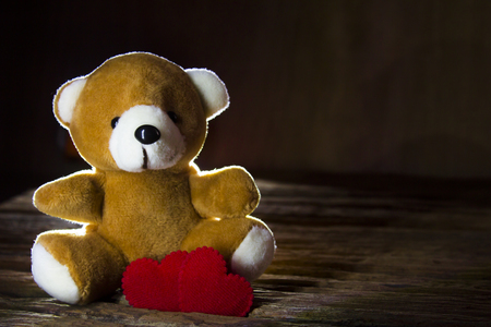 Valentine's day concept teddy bear and two red hearts symbol on wood floor background,copy space for text,light and shadow style.
