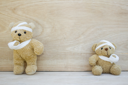 Two Teddy bear with bandages and broken hand on wood background,copy space, 免版税图像