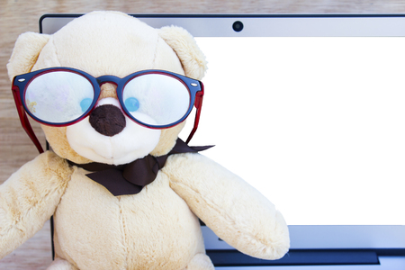 cute teddy bear wear glasses and side view laptop computer on wood background with copy space for text. Foto de archivo