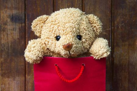 Lindo oso de peluche en bolsa de regalo roja sobre fondo de madera, concepto de día de San Valentín. Foto de archivo