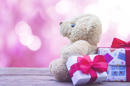 cute teddy bear and gift box  on wooden mock up over pink bokeh background with copy space,valentine's day concept.