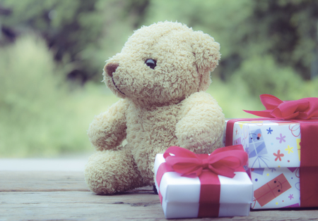 Cute teddy bear with gift box on old wood background,Christmas and New Year's Day concept,vintage style.