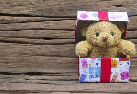 Cute teddy bear in gift box on old wood background with copy space,Christmas and New Year's Day concept.