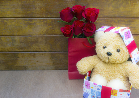 Cute teddy bear in the gift box with red roses in gift bag on old wood background, New Year's Day and Valentine's Day concept,copy space.