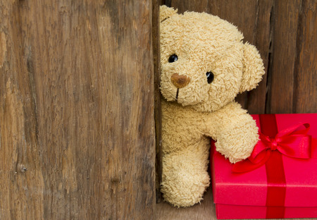 Cute teddy bear with red gift box on old wood background with copy space,Christmas and New Year's Day concept.