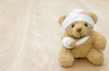 Teddy bear with bandages and broken arm on wood background,copy space. 免版税图像