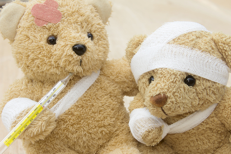 Teddy beas with bandages and thermometer on wood background with copy space. 免版税图像
