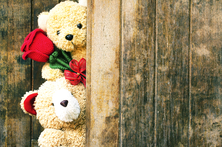 Valentine's day concept with Cute teddy Bears toy clutching a red rose in its arms on wooden background for an anniversary or valentine's celebration, copy space.