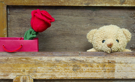 Valentine's day concept with Cute teddy Bear toy with red rose in red gift bag on old wood background for an anniversary or valentine's celebration, copy space.