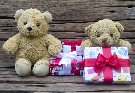 Cute teddy bears with gift box on old wood background,Christmas and New Year's Day concept.