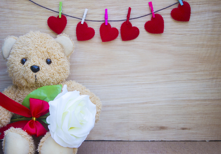 Valentine's day concept with Cute teddy Bear toy clutching a white rose in its arms on wooden background for an anniversary or valentine's celebration, copy space.