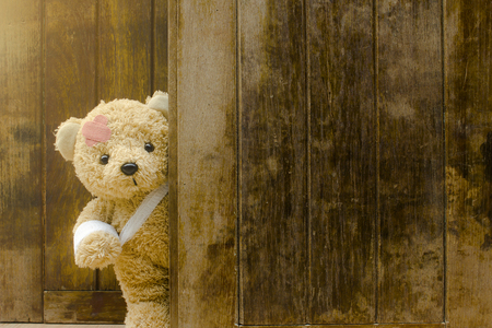 Teddy bear with bandages and broken hand on wood background,copy space.