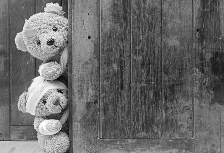 Teddy bears with bandages and broken hand on wood background,copy space,tone black and white. 免版税图像