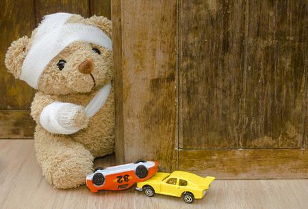 Teddybeer met pleisters en speelgoedauto ondersteboven op hout achtergrond met kopie ruimte, ongeval concept. Stockfoto