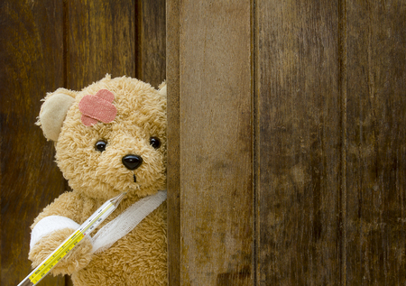 Teddy bear with bandages and thermometer on wood background with copy space.