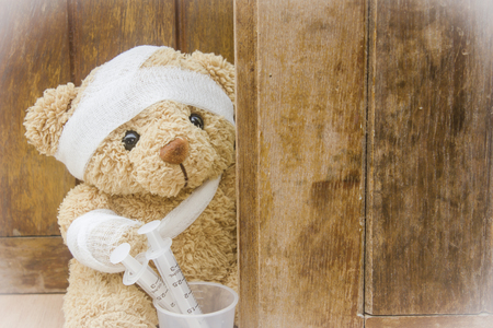 Teddy bears with bandages and syringes on wood background,copy space. 免版税图像