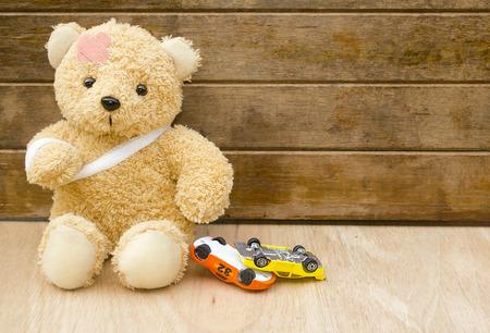Teddybeer met pleisters en speelgoedauto's ondersteboven op hout achtergrond met kopie ruimte, ongeval concept.
