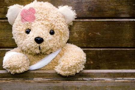 Teddy bear with bandages and broken hand on wood background,copy space, 免版税图像