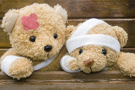 Teddy bears with bandages and broken hand on wood background,copy space.