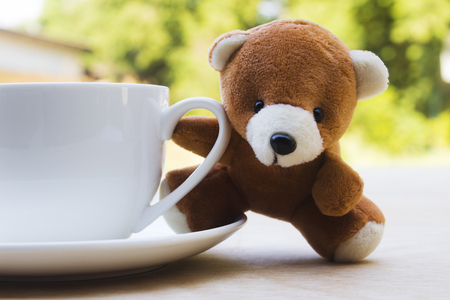 teddy bear and white cup coffee on wood table on natrue bokeh background. 免版税图像