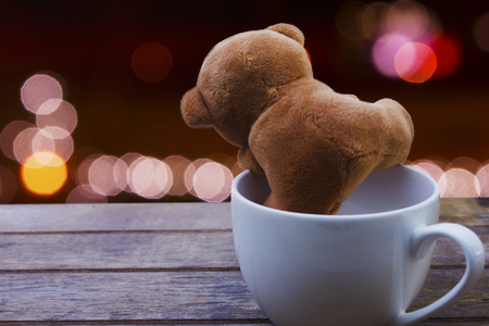 teddy bear in white cup coffee on wood table on night bokeh background with copy space.