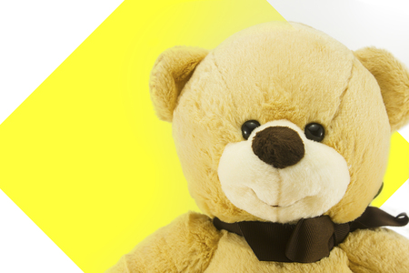 close up cute teddy bear on yellow paper and white background with copy space.