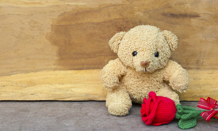Valentine's day concept with Cute teddy bear and red rose in gift bag on wooden background for an anniversary or valentine's celebration. 免版税图像