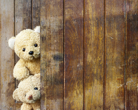 Cute teddy bears on wooden background with copy space.