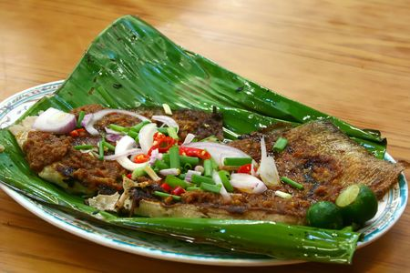 BBQ stingray on banana leaf garnished with spring onions, onions, red chillies and lime on a plate Stock Photo