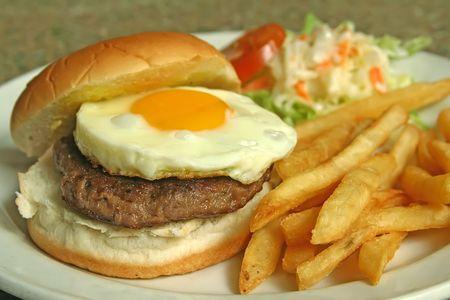 Una atractiva foto de hamburguesa con huevo, fritas y col.  Foto de archivo - 2410277