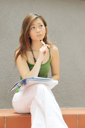 Asian Lady Thinking and Curious with Pen photo