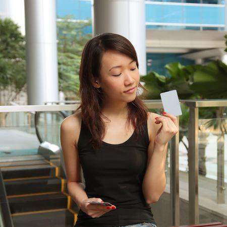 Asian Lady Holding a Credit Card or Pass Stock Photo - 5306706