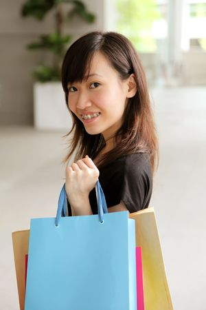 Asian Teenager Female With Shopping Bags in Mall photo