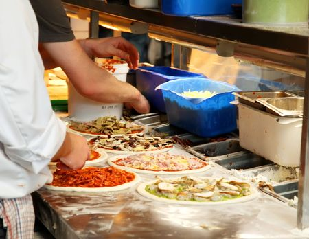 preparing dough: Different Pizzas Being Made in a Kitchen
