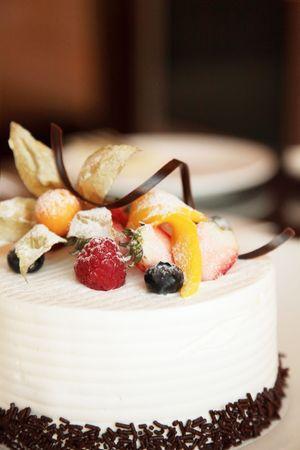porcion de torta: Crema blanca la guinda del pastel con frutas y chocolate