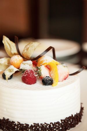 White Cream Icing Cake with Fruits and Chocolate photo