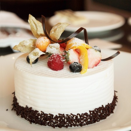 cake with icing: White Cream Icing Cake with Fruits and Chocolate Stock Photo