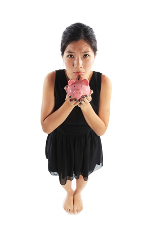 education loan: Sad Asian Chinese with Piggy Bank Pouting Stock Photo