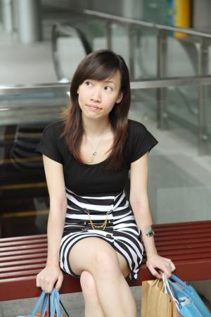 asian shopper: Asian Female Shopper Sitting Resting with Shopping Bags