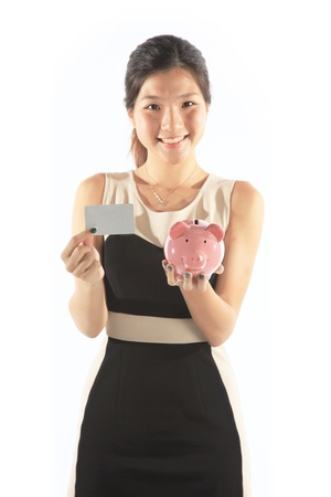 Asian Lady Holding Piggy Bank and Credit Card on White photo