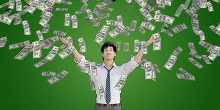 raining: Hombre asiático Dinero de cogida que caen del cielo en dólares estadounidenses Foto de archivo