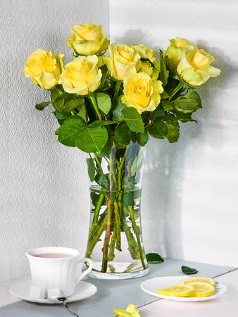 Naturaleza muerta con un ramo de rosas amarillas y una taza de té Foto de archivo