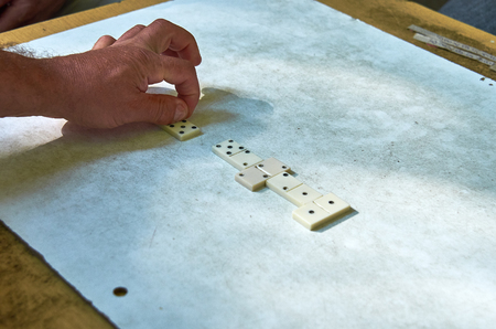 top view of the hands of adults playing dominoes Stock Photo