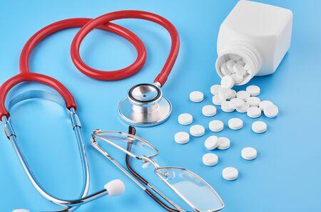 Pills tablets capsules closeup. On a blue background, a jar of medicine. On a blue background, a jar of medicine and a stethoscope. Medical concept for your design. Фото со стока