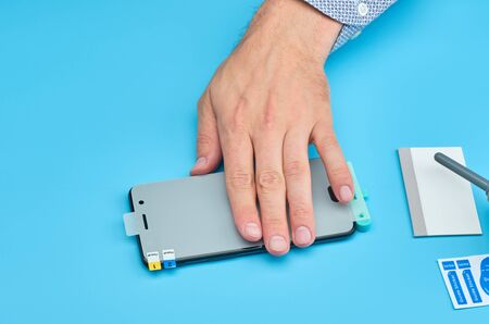 Hand of man replacing the broken tempered glass screen protector for smartphone.
