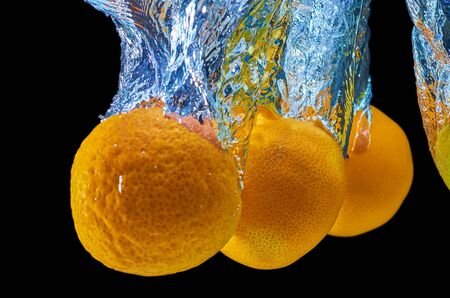 Fresh orange, mandarine falling in water with splash on black background. Stock Photo
