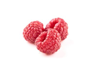 Three red raspberry berries isolated on white background.