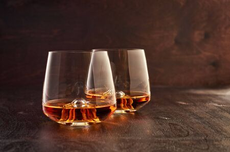 Two crystal glasses of whiskey on a wooden table. Фото со стока
